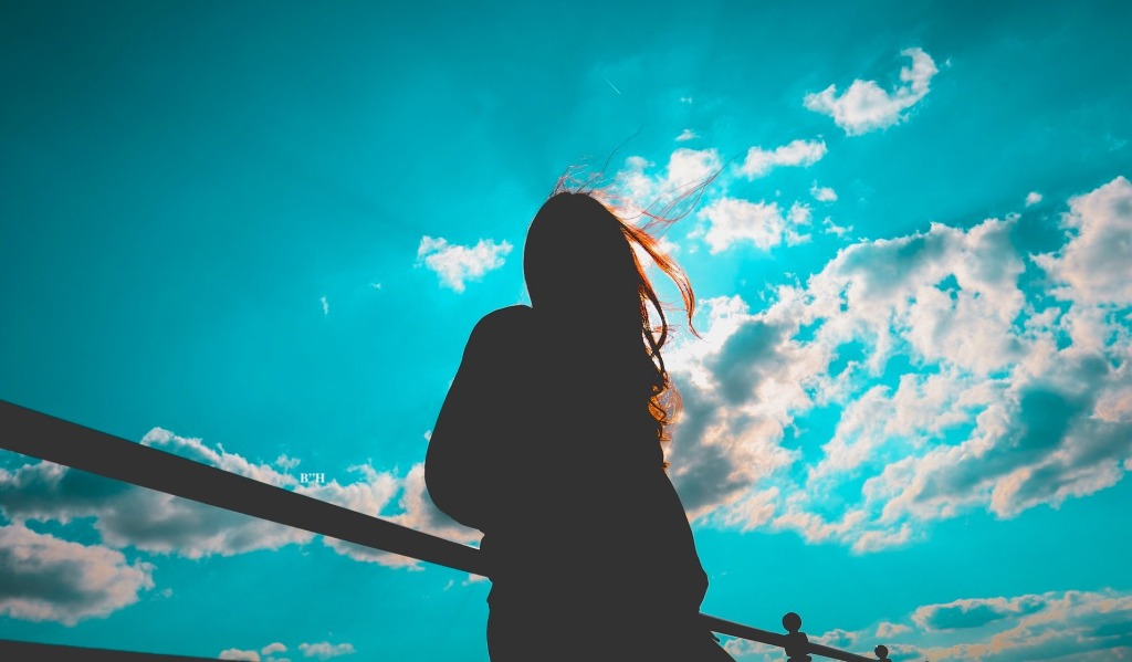 woman alone looking at sky and clouds